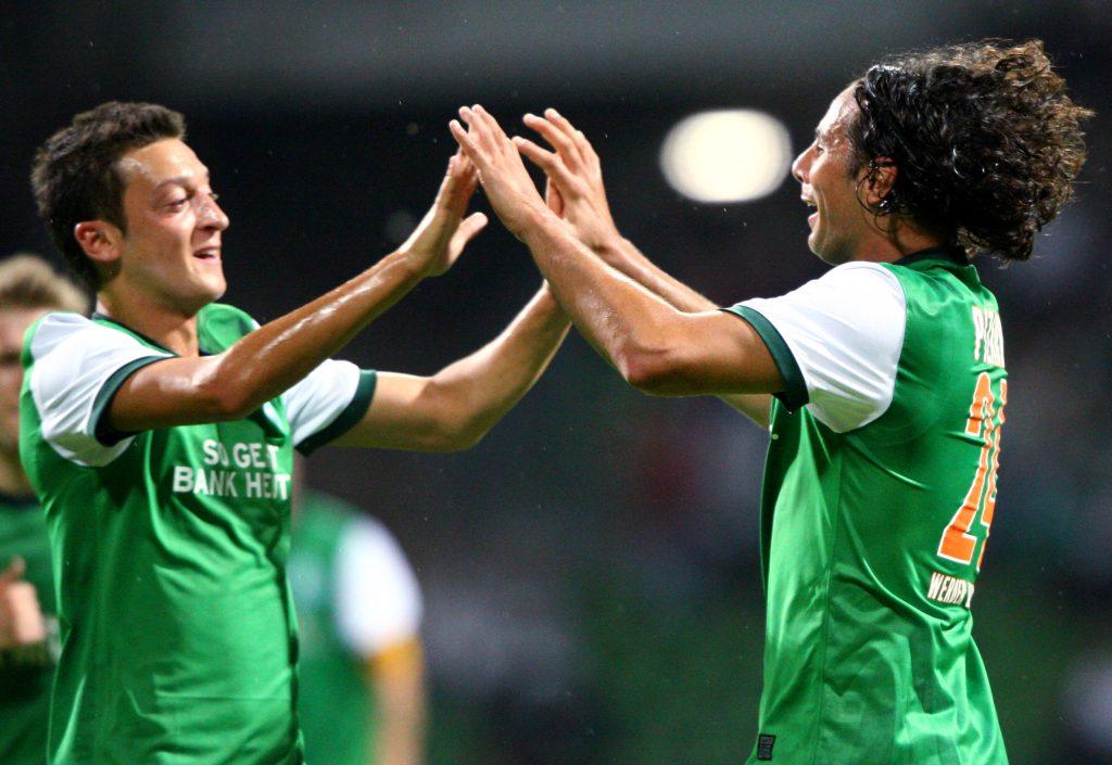 Mesut Ozil celebrates with a Werder Bremen teammate